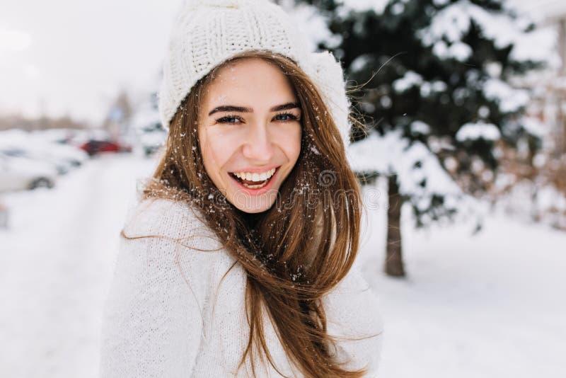 Spektakulär långhårig kvinna som skrattar, medan posera på snöbakgrund Utomhus- närbildfoto av den caucasian kvinnliga modellen royaltyfri foto