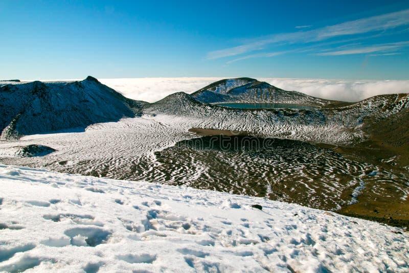 Spektakulär scenisk sikt av det snöig landskapet för lösa berg med den djupblå sjön ovanför molnen, nyazeeländsk Tongariro nation royaltyfria bilder