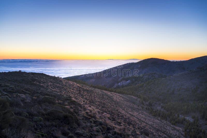 Spektakulär solnedgång ovanför molnen i den Teide vulkannationalparken arkivfoton