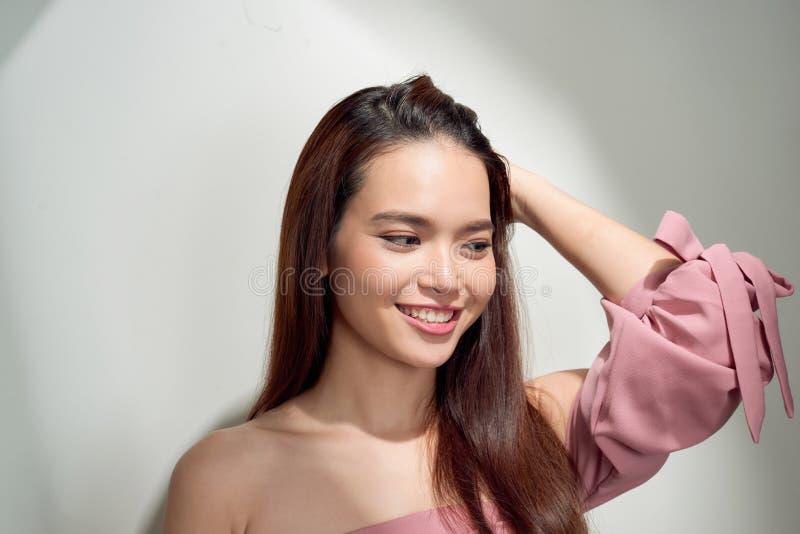 Spektakul?r asiatisk ung kvinna som spelar med hennes h?r Inomhus foto av den underbara kvinnliga modellen på vit bakgrund royaltyfri foto