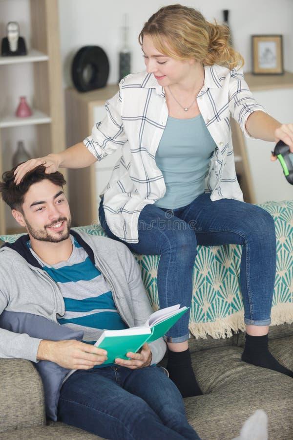 Spel van de vrouwen het speel opwindend computer en man lezingsboek stock foto's