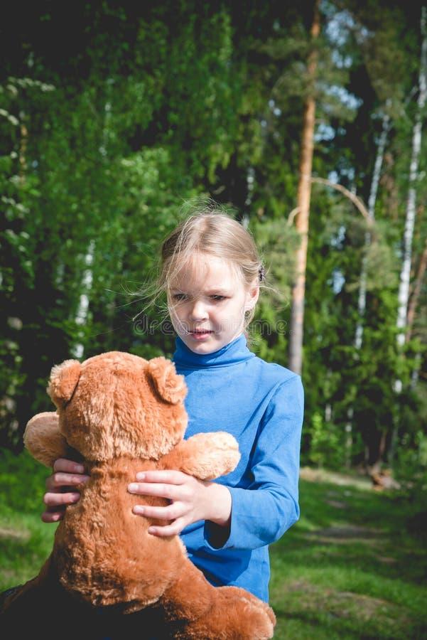 Spel van het Llittle het leuke meisje met teddybeer op de zomer in openlucht Beste vriendenconcept Beste vriendenconcept royalty-vrije stock foto's