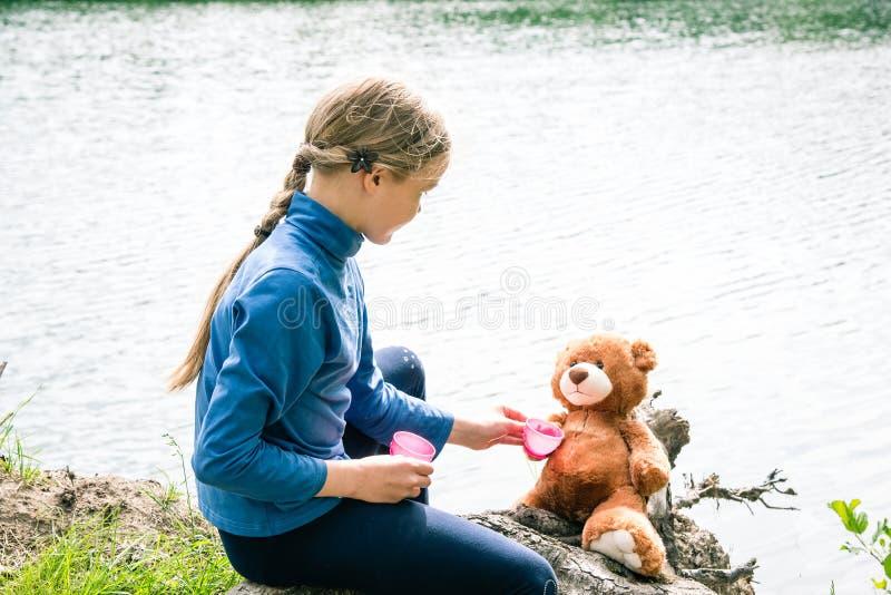 Spel van het Llittle het leuke meisje met teddybeer op de zomer in openlucht Beste vriendenconcept Beste vriendenconcept Het uits royalty-vrije stock foto's