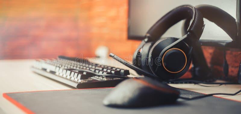 Spela arenabakgrund med datoren för muskugghjulhörlurar, valde focuse på hörlurar det långa banret för focuse royaltyfria bilder