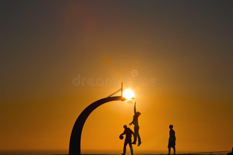 Spela basket på solnedgången med naturlig himmelbakgrund arkivbild