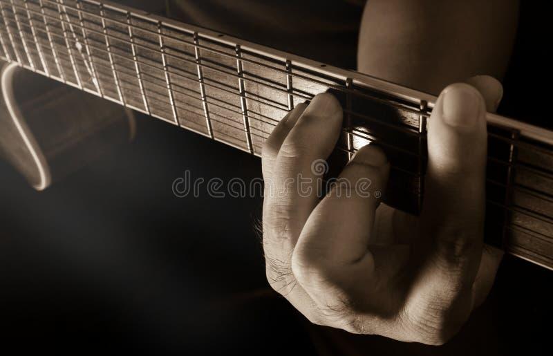 Spela den akustiska gitarren, gitarristen eller musikern arkivbild