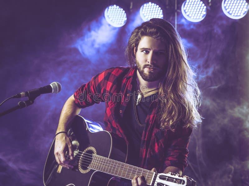 Spela den akustiska gitarren på etapp royaltyfri foto