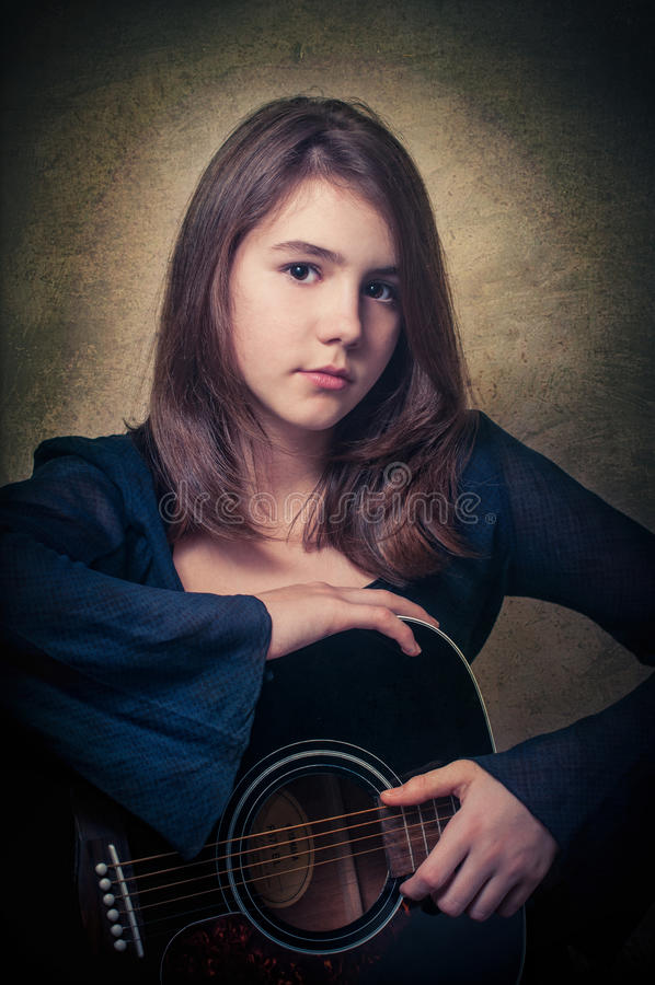 Spela den härliga tonåriga flickan för gitarren som… spelar musik med en gitarr arkivbild