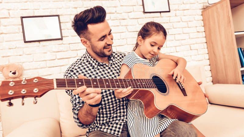 Spela den härliga tonåriga flickan för gitarren som… spelar musik med en gitarr  piano för bakgrundsgitarrmusik FaderAnd Daughte royaltyfri fotografi