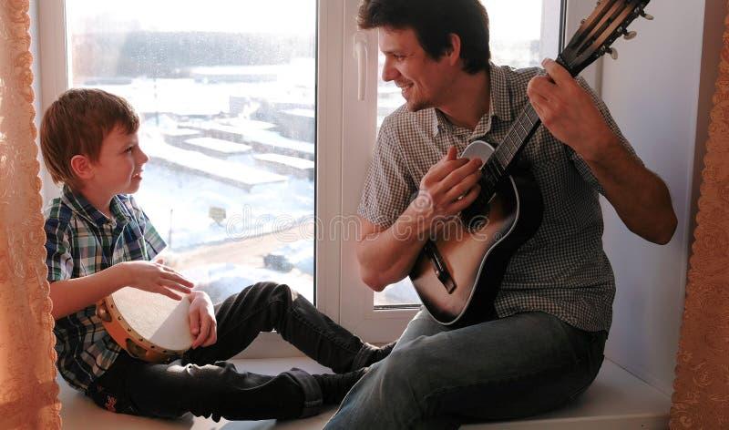 Spela ett musikinstrument Farsan spelar gitarren, och sonen spelar tamburinsammanträde i fönsterbräda fotografering för bildbyråer
