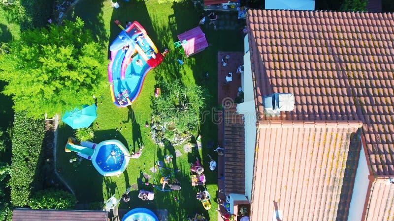 Spela för barn som är utomhus- i en husträdgård, över huvudet sikt royaltyfria bilder