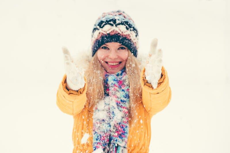 Spela för hatt och för halsduk för ung kvinna bärande lyckligt le med utomhus- snö royaltyfria foton