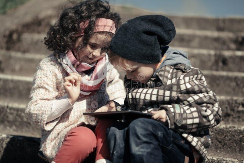 Spela för liten flicka som och för pojke är utomhus- fotografering för bildbyråer