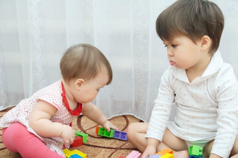 Spela för systrar Två små flickor, behandla som ett barn och lilla barnet svartsjukt barn fotografering för bildbyråer