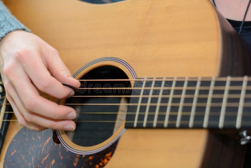 Spela gitarren, assistent - närbild arkivfoton
