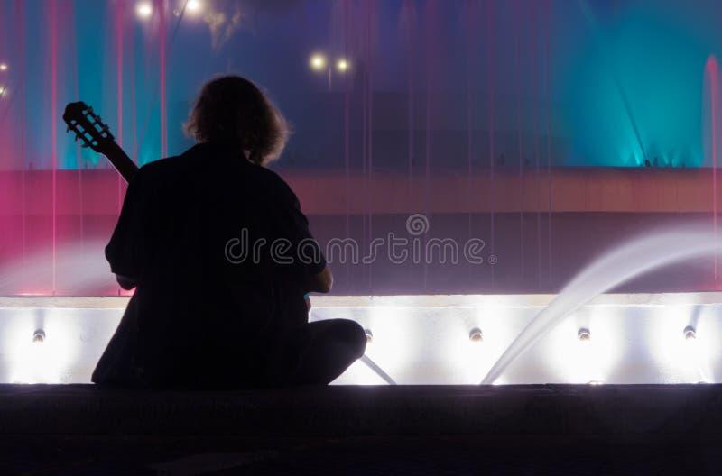 Spela gitarren på natten royaltyfri bild