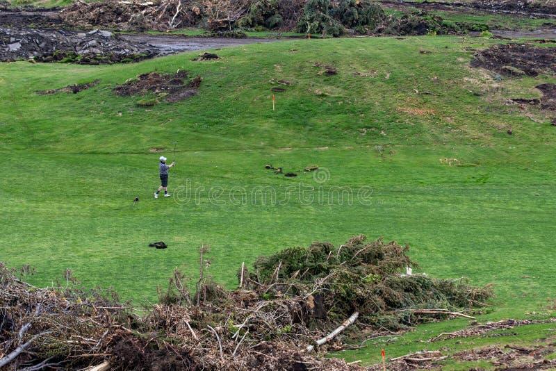 Spela golf på en farled som öronmärkas för ny inhysa utveckling royaltyfria bilder