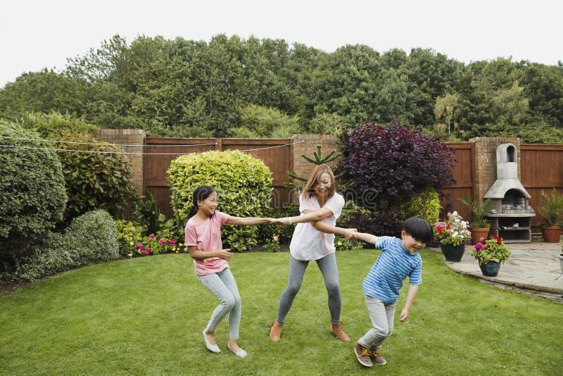 Spela i trädgården med mumen arkivfoto