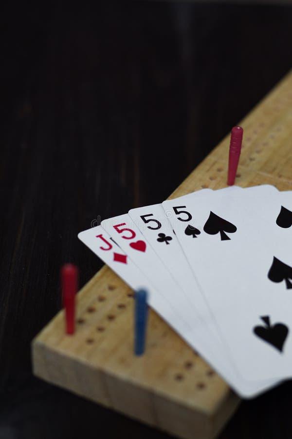 Spela kort och cribbagebräde på svart bakgrund arkivbild