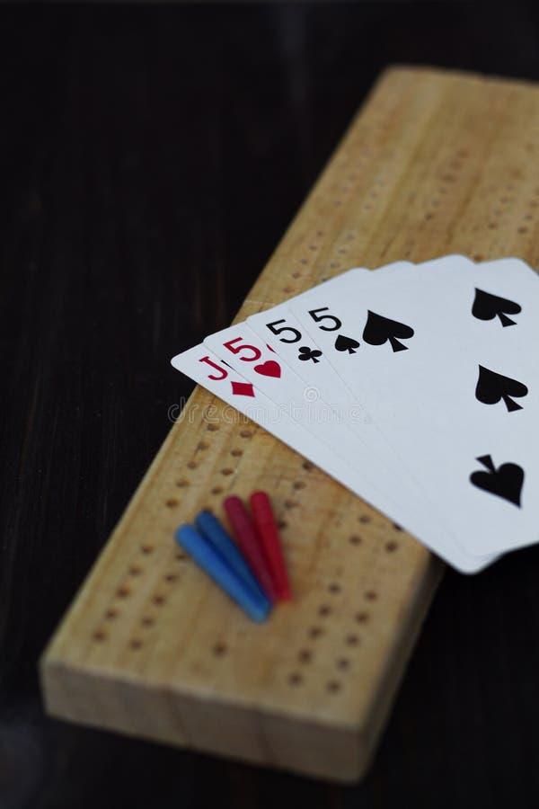 Spela kort och cribbagebräde på svart bakgrund arkivfoto