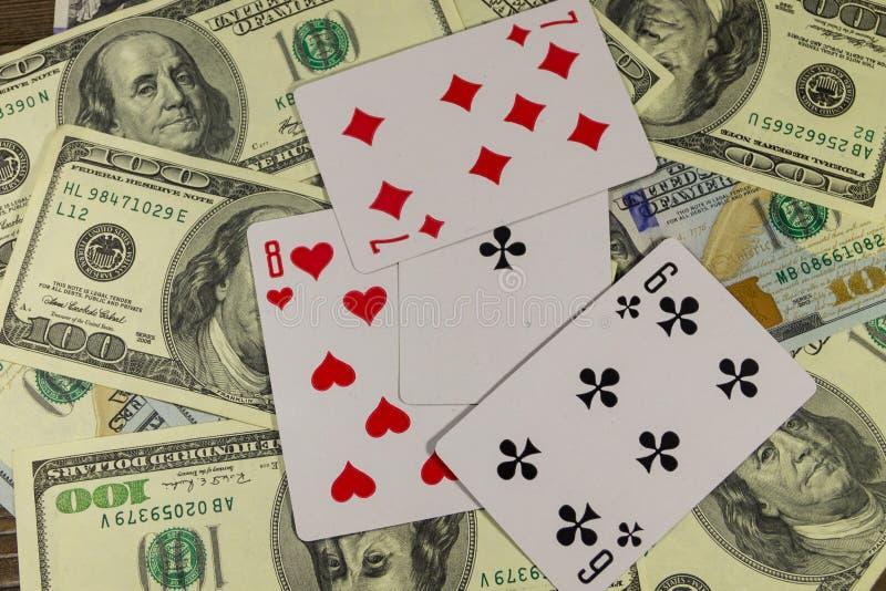 Spela kort på amerikan hundra bakgrund för dollarräkningar royaltyfria foton