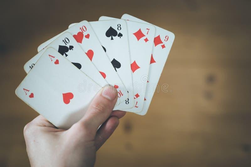 Spela kort: Pokerkort i handen av en man royaltyfri bild