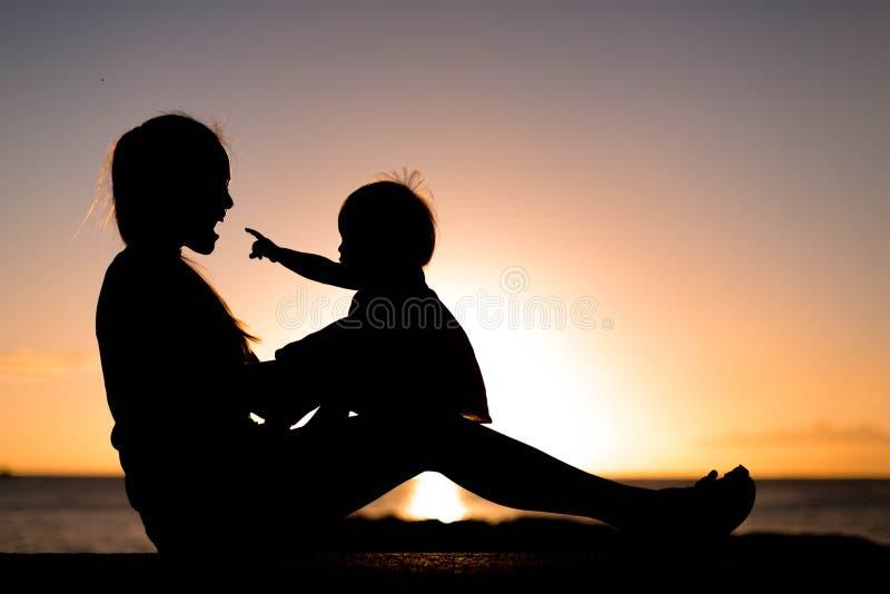 Spela och hållande ögonen på solnedgång för moder och för barn på stranden i kontur arkivfoto