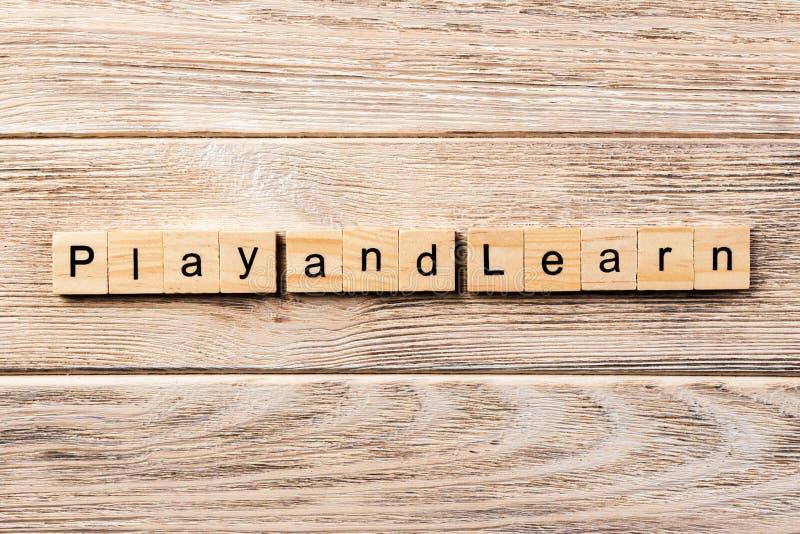 Spela och lär ordet som är skriftligt på träsnittet spela och lär text på tabellen, begrepp fotografering för bildbyråer