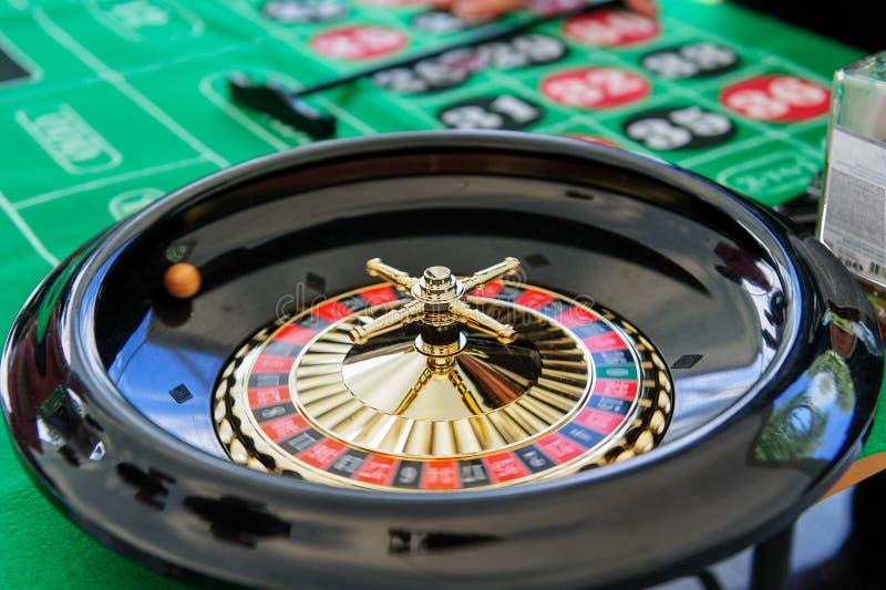 Spela rouletten i en kasino på en grön tabell royaltyfri fotografi