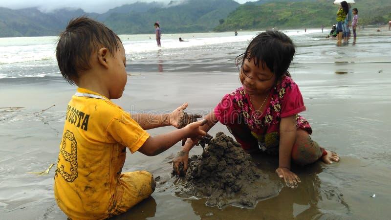 Spela sätter på land sander i sommarstrand` Sidem Tulungagung Indonesien `, royaltyfria foton