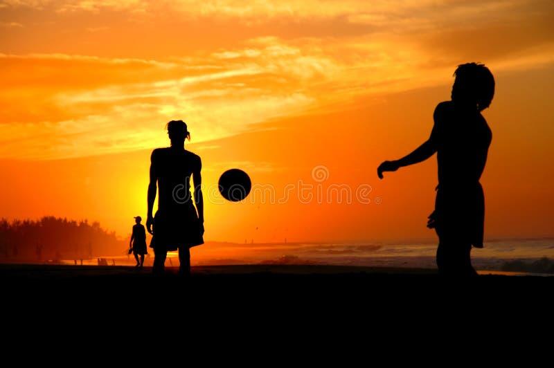Spela som är footbal på solnedgången på stranden arkivbild