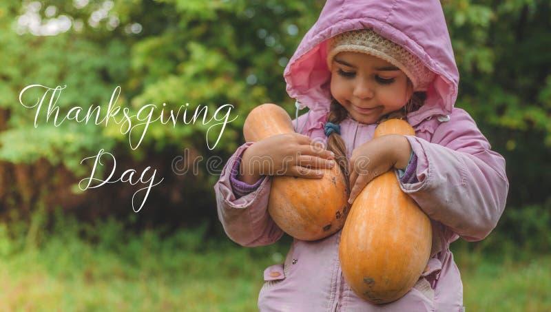 Spela utomhus den gulliga lilla flickan som rymmer en pumpa Skörd av pumpor, den älskvärda flickan och stora pumpor Begreppsmässi arkivbild