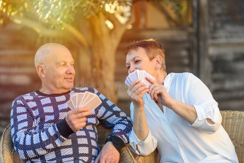 Spelar spela kort för höga gamla par på parkerar på solig dag royaltyfria foton