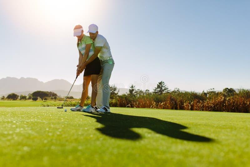 Spelare för golf för manlig golfinstruktörundervisning kvinnlig arkivfoton