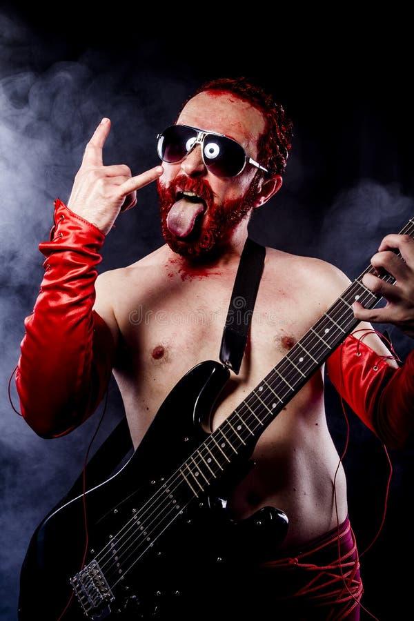 Spelare gitarrist med svart för elektrisk gitarr, bärande framsidamålarfärg royaltyfri bild