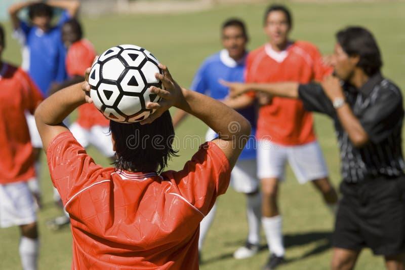 Spelare ordnar till för att kasta fotboll royaltyfri foto
