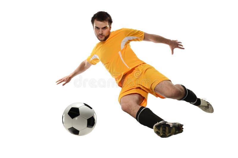 Spelare som sparkar fotbollbollen arkivbilder