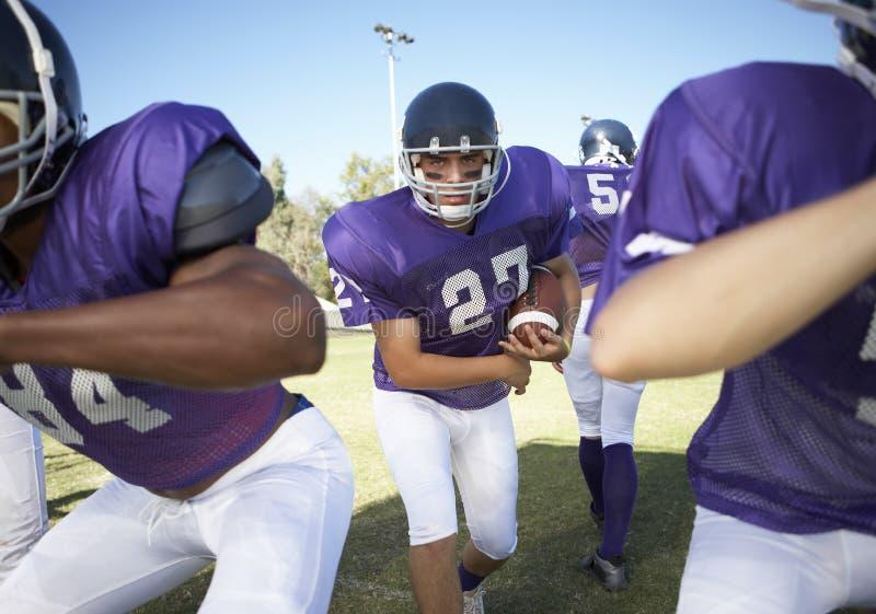 Spelare som spelar amerikansk fotboll på fält arkivfoto