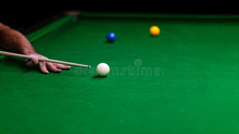 Spelarehand med stickrepliken och bollar på en grön torkduk arkivfoton