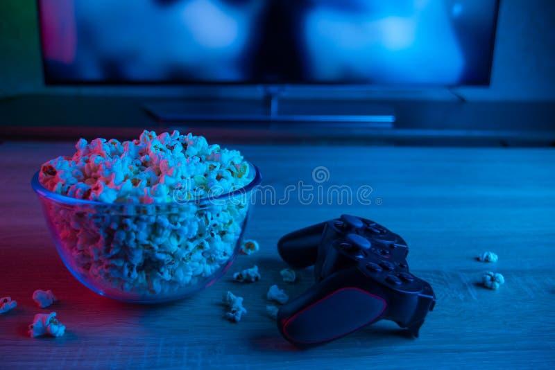 Spelbedieningshendel van de console of PC met een kom popcorn op de achtergrond van een TV of een monitor Met blauwe en rode kleu royalty-vrije stock foto