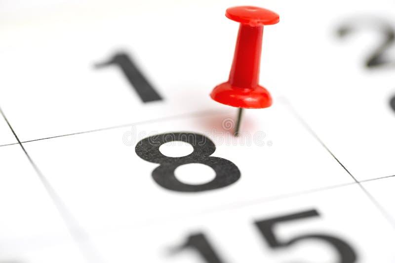 Speld op de datum nummer 8 De achtste dag van de maand is duidelijk met een rode punaise Speld op kalender Kalenderconcept voor stock foto's