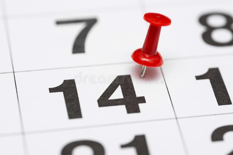Speld op de datum nummer 14 De veertiende dag van de maand is duidelijk met een rode punaise Speld op kalender stock foto