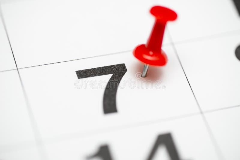 Speld op de datum nummer 7 De zevende dag van de maand is duidelijk met een rode punaise Speld op kalender royalty-vrije stock afbeeldingen