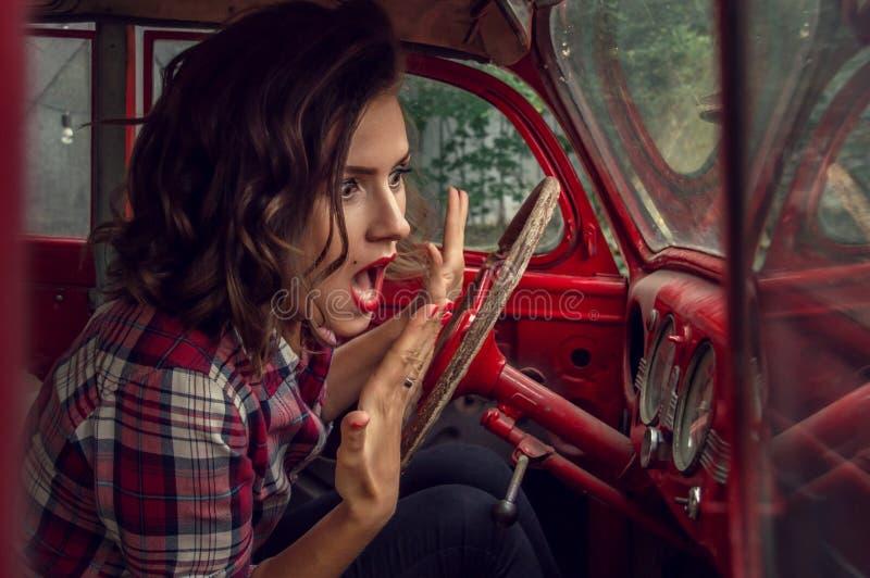 Speld-op meisje in een plaid wordt het overhemd bang gemaakt en het gillen, bekijkend de snelheidsmeter in de cabine van oud aang stock fotografie