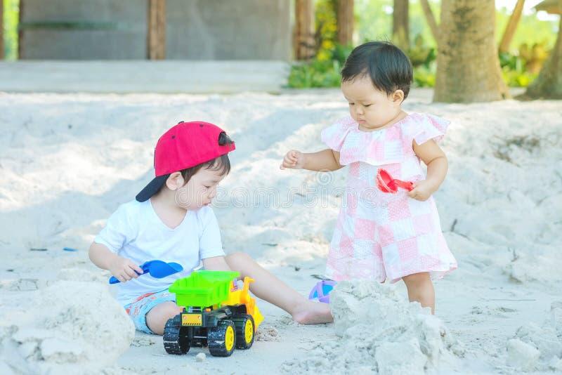 Spelen het de close-up leuke Aziatische jongen en meisje met zand en stuk speelgoed op strand geweven achtergrond stock afbeeldingen