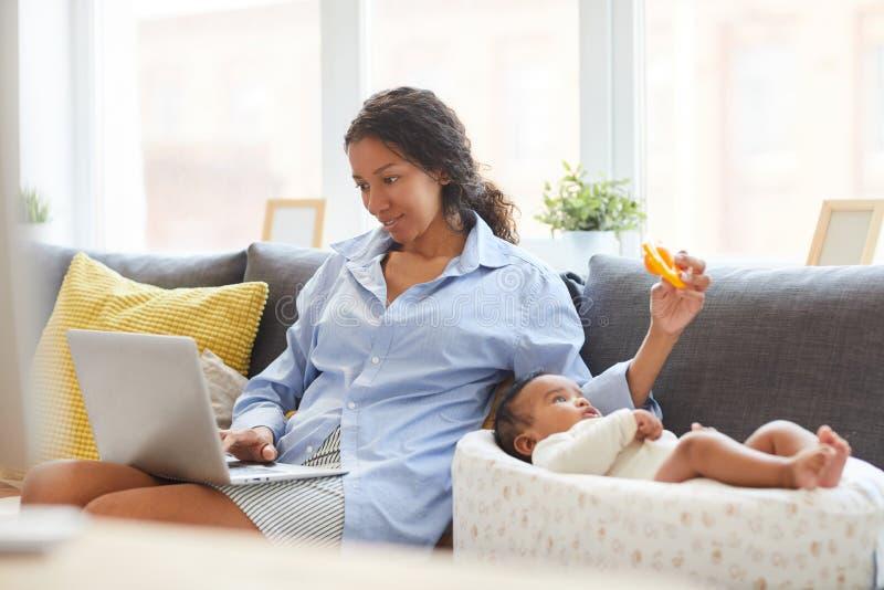 Spelen met baby terwijl het gebruiken van laptop stock afbeeldingen