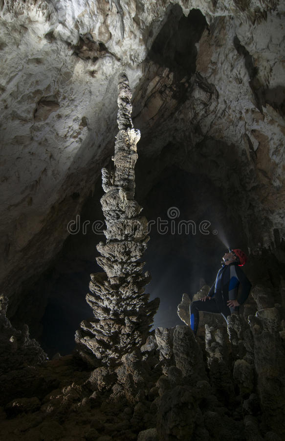 Man in diving wet suite admiring big stalagmite in. Very nice scene in a cave with man in a wet diving suite with a red helmet admiring a big stalagmite witch royalty free stock photography