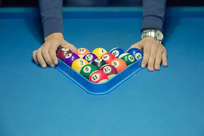 Speler die driehoek gebruiken aan het voorbereiden van de ballen voor het volgende spel stock afbeelding