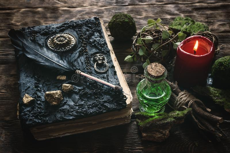 Book of magic. Spell book, magic potion and other various witchcraft accessories on the wizard table background royalty free stock photos