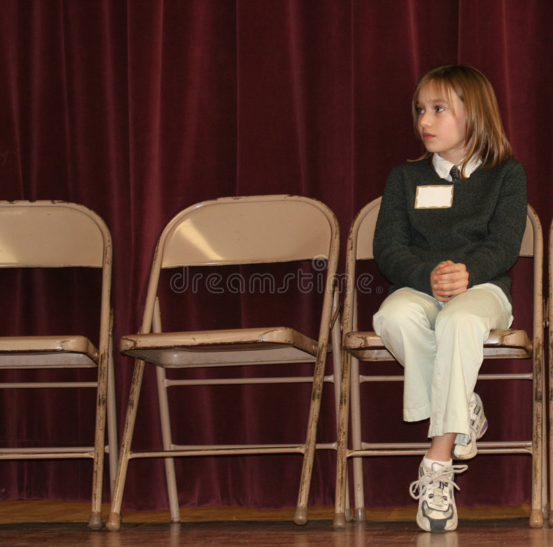 Spelling Bee. Young girl sitting in chair near end of elementary school spelling bee royalty free stock photo